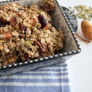 Best Crunchy and Chunky Granola in a baking dish with a tablespoon of cinnamon